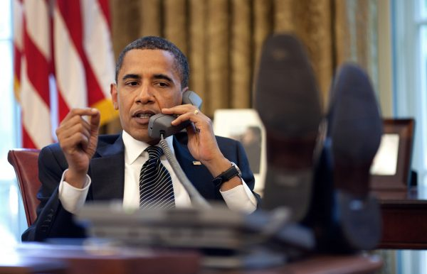 Picture of President Obama on the phone in the Oval office, with feet on desk.  Is he Converting a Lead?
