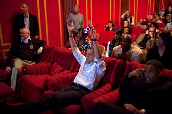 President Obama is in a media theater room with hands in air, cheering a touchdown in Superbowl game.  Is he managing his staff, or having a party?