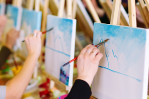Individuals hold paint brushes and paint mountains on a canvas.