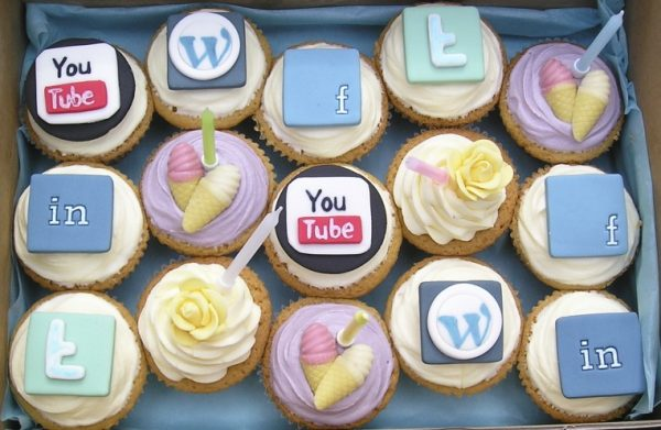 Box of cupcakes with social media icons as toppings to represent ways to make your social media post delectable for the audience to pick it up and share there by improving organic reach on social media